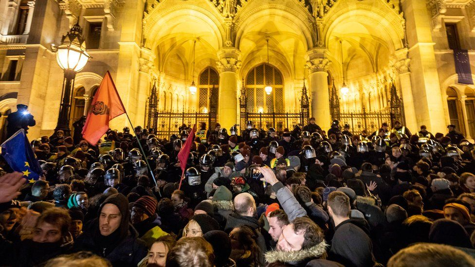 A large crowd presses against the line of riot police in front of the parliament building in Budapest