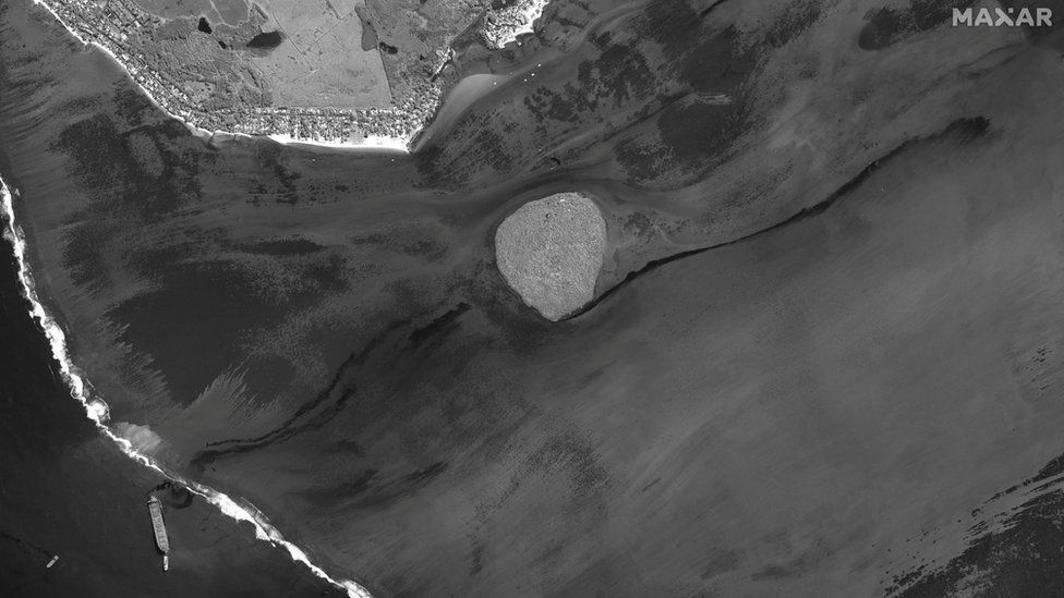 A satellite image shows the ship and the oil spill
