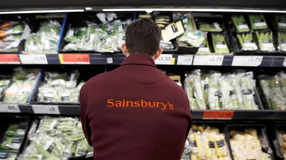 A Sainsbury's worker stacks a vegetable shelf in a store