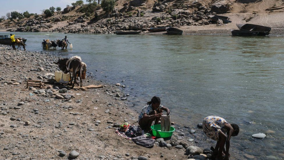 Refugees from the Tigray region of Ethiopia wash their clothes on the Sudanese bank of the Tekeze River with Sudanese locals on December 5, 2020 in Hamdayet, Sudan.
