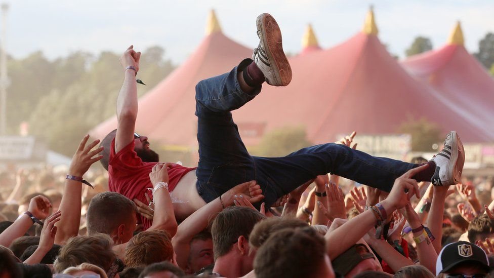 A person crowdsurfing at Reading festgival