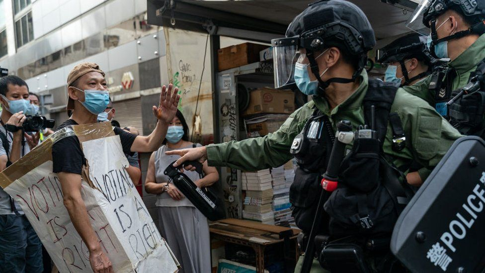 A man wearing a Voting Is A Right costome stand off with riot police during an anti-government protest on September 6, 2020 in Hong Kong