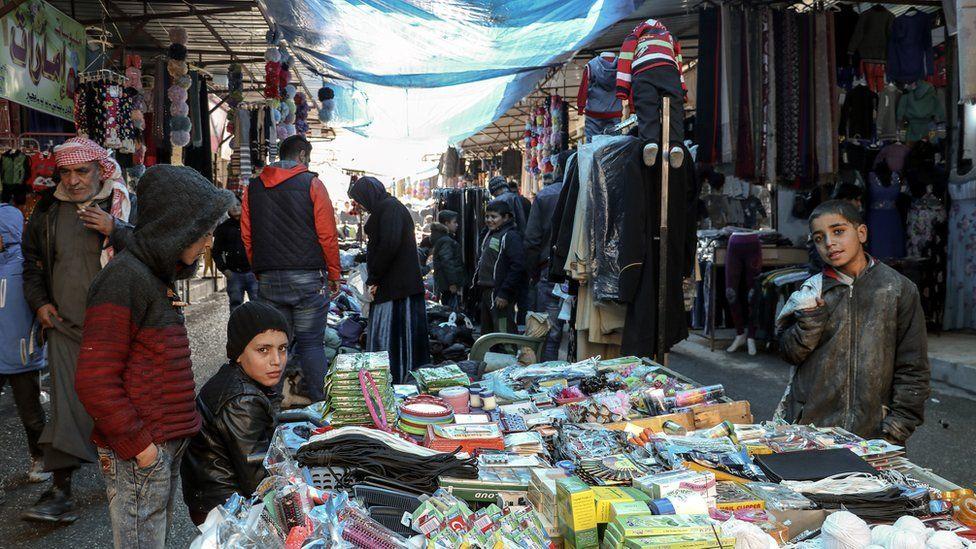 Syrians walk in a popular market in Manbij, northern Syria (31 December 2018)