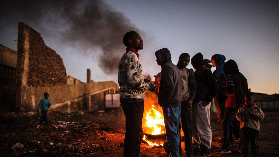 Residents of the Kliptown section of Soweto gather next to burning tyres during a service delivery demonstration on July 27, 2016 ahead of August 3rd municipal elections.