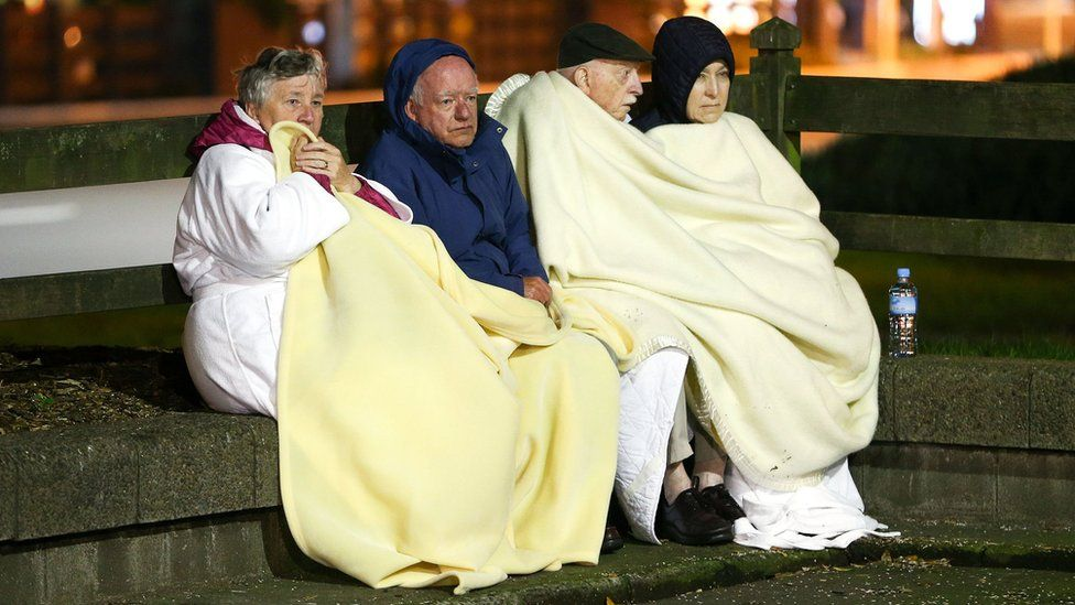 Four people sit on a low wall under blankets after the earthquake