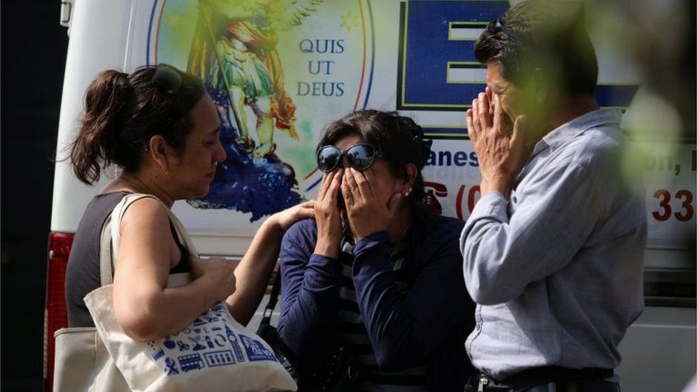 Relatives of the victims of a bus that crashed with a truck and careened off a cliff along a sharply curving highway north of Lima, wait outside a hospital morgue in Chancay, Peru, January 3, 2018.