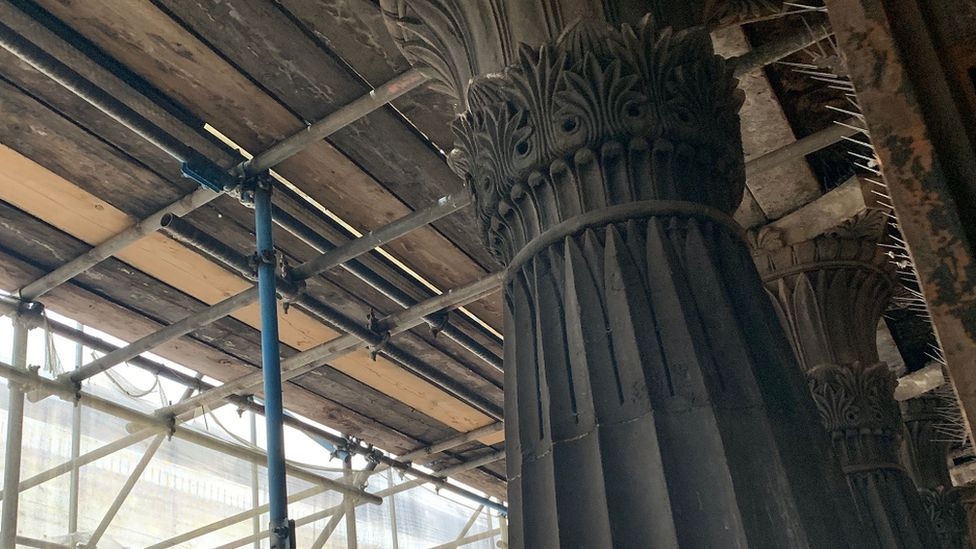 A column with scaffolding in the background