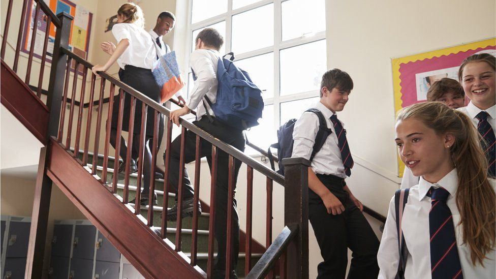 School pupils walking up stairs