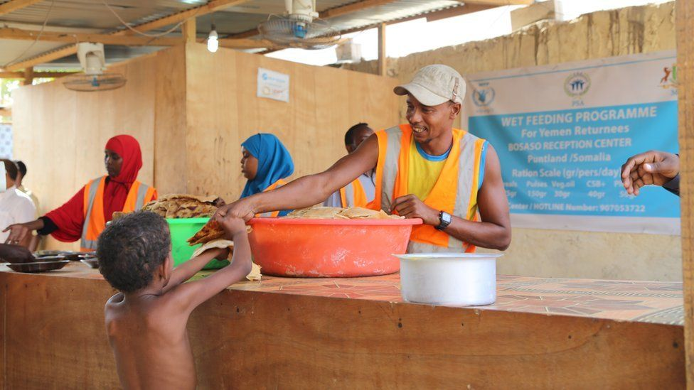 A boy is handed some food at a feeding programme, Bossasso, Somalia
