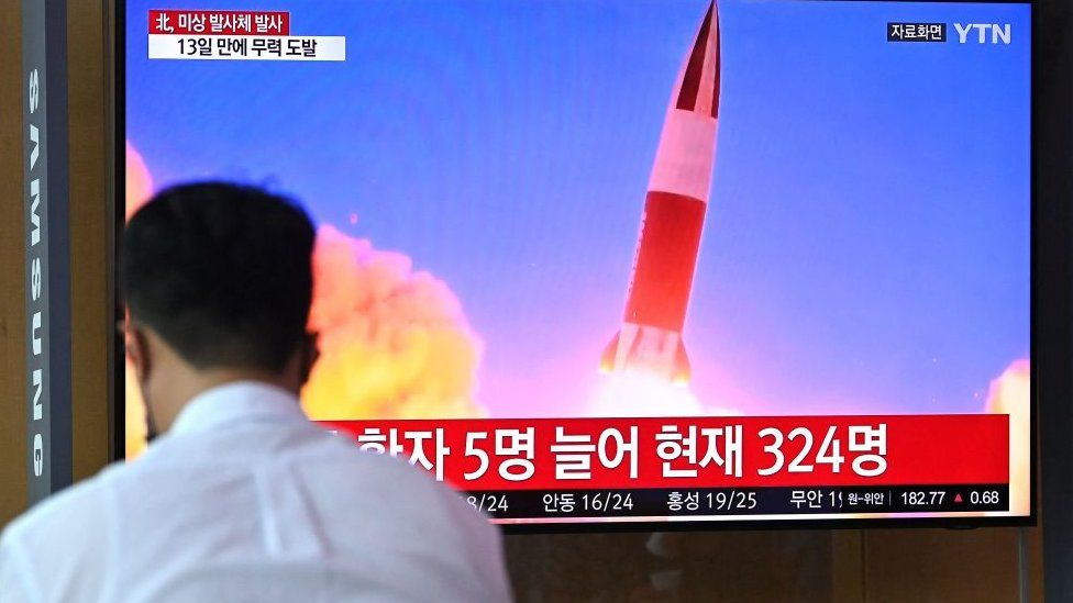People watch a television news broadcast showing file footage of a North Korean missile test, at a railway station in Seoul on September 28, 2021