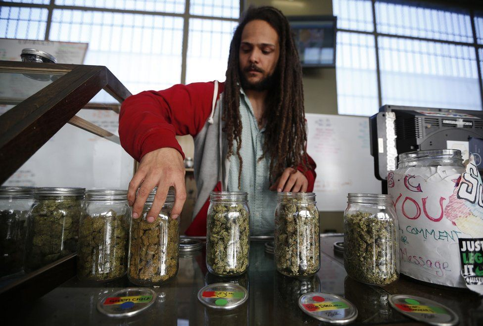 Volunteer Charlie Kirchheimer displays jars of dried cannabis buds at the La Brea Collective medical marijuana dispensary in Los Angeles