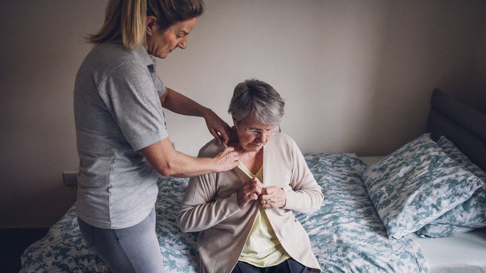 A carer helping a female client in her bedroom