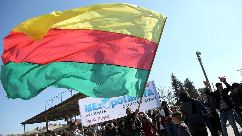 A Kurdish man waves the flag of the Kurdish Democratic Union Party (PYD) at a protest in Qamishli, Syria (4 February 2016)