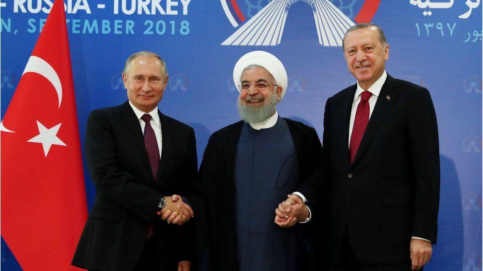 Russian President Vladimir Putin (L), Iranian President Hassan Rouhani (C) and Turkish President Recep Tayyip Erdogan (R) shake hands in Tehran (7 September 2018)