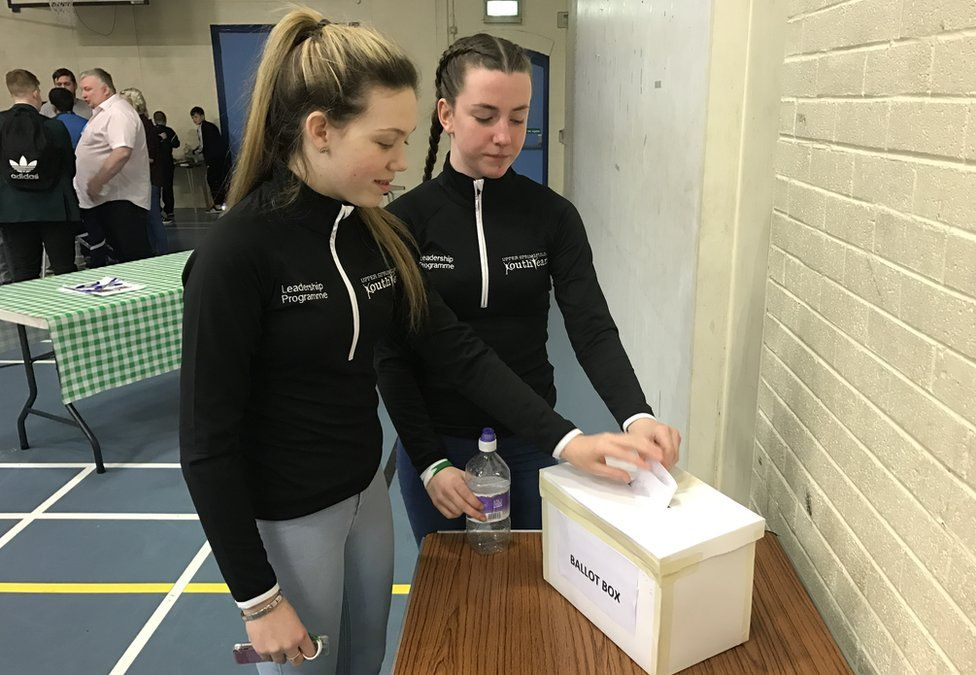Two girls place their votes in a ballot box