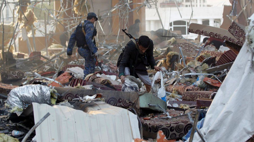 A Yemeni collects items amidst the rubble of a destroyed building following an attack in the capital Sanaa on 8 October