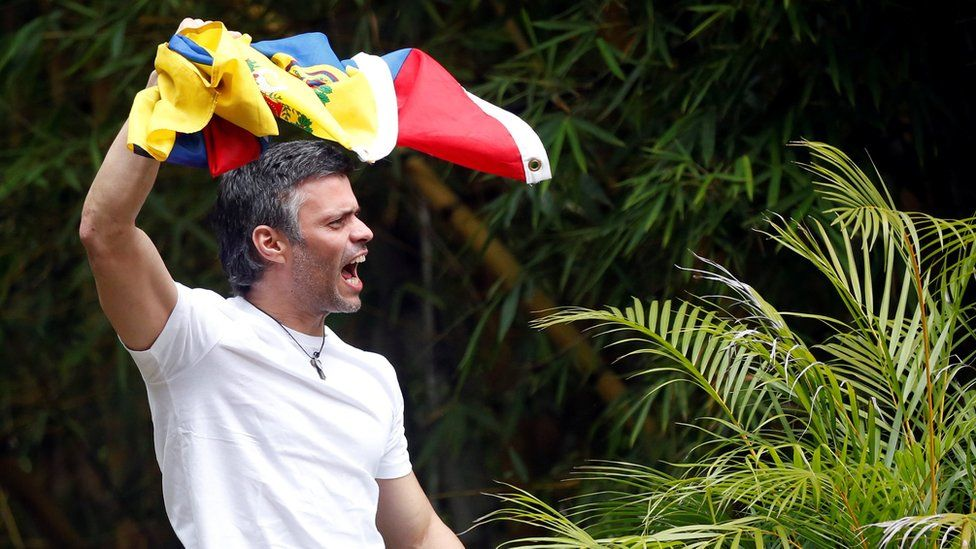 Leopoldo López climbed on his roof to greet supporters after being released from prison to house arrest, 8 July