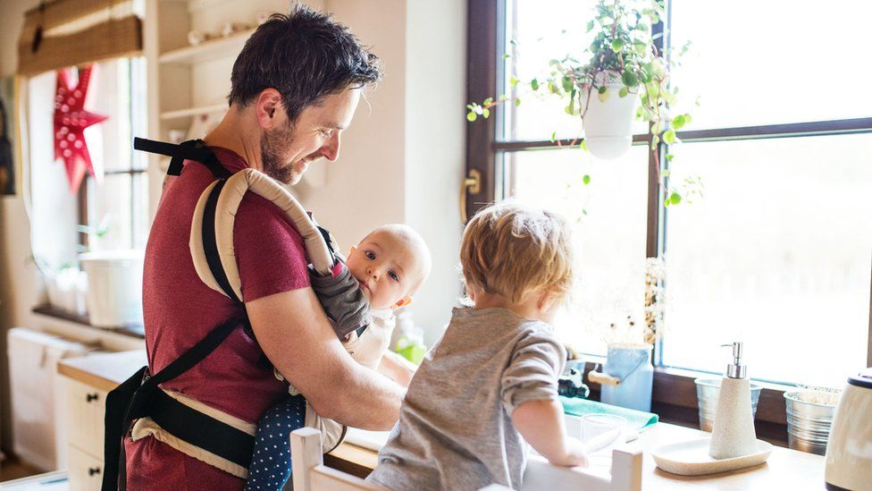 A father with a baby and a toddler