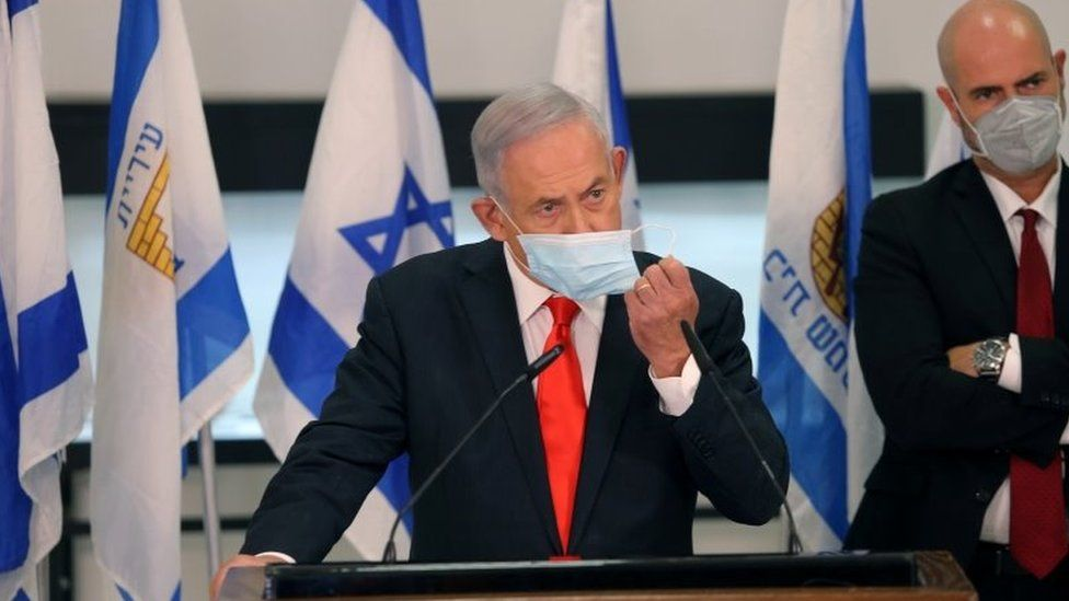 """Israeli Prime Minister Benjamin Netanyahu adjusts his face mask while announcing night-time curfews in 40 """"red"""" areas (8 September 2020)"""