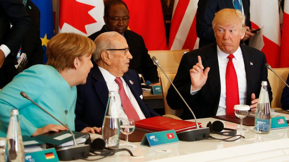 President Trump talks to German Chancellor Angela Merkel (L) and Tunisia's President Beji Caid Essebsi at the G7 summit expanded session in Taormina, Sicily,May 27, 2017