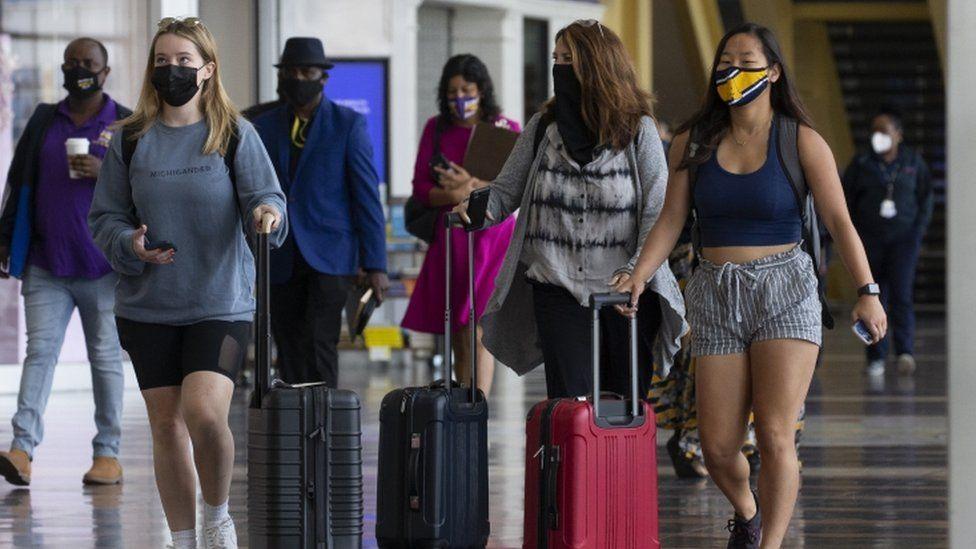 Air passengers walk through a terminal at Ronald Reagan Washington National Airport in Arlington, Virginia