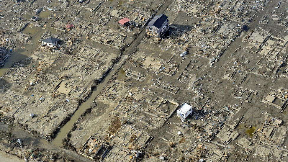 An aerial picture shows just a couple of buildings standing amid blocks of devastation in the town of Ishinomaki (Getty Images)