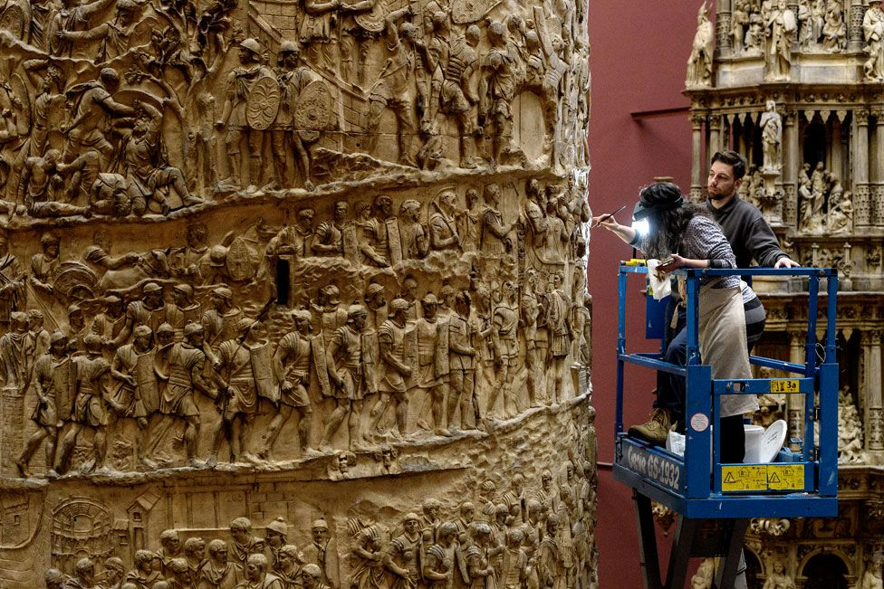 A museum worker stands on a cherry-picker whilst working on a large decorated column