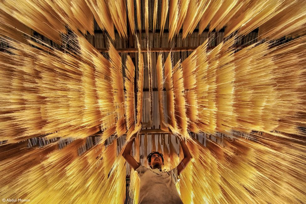Man reaching up to rice noodles that are hanging above him