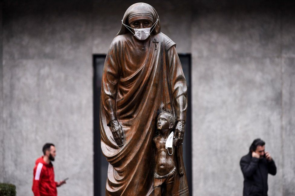 Face masks are placed on the statue of Saint Teresa