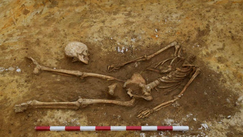 A decapitated Roman skeleton with the skull placed by the knees