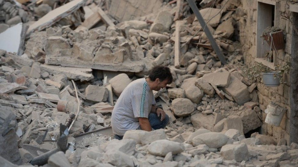 A man reacts to his damaged home after a strong earthquake hit Amatrice on August 24, 2016