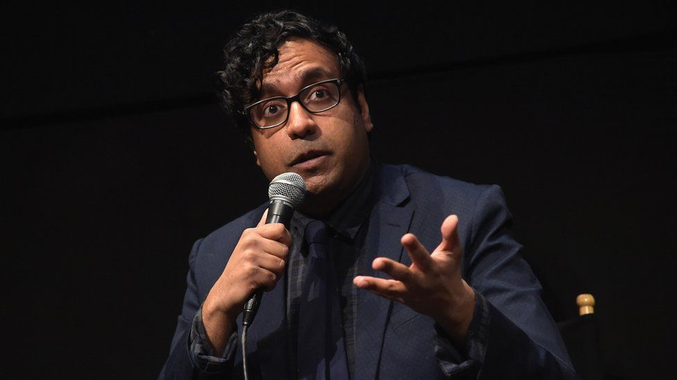 Hari Kondabolu pictured with a microphone at screening of his documentary