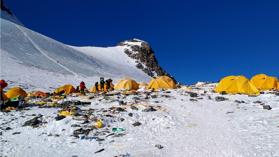 Next to yellow tents, discarded climbing equipment and rubbish left scattered at Camp 4