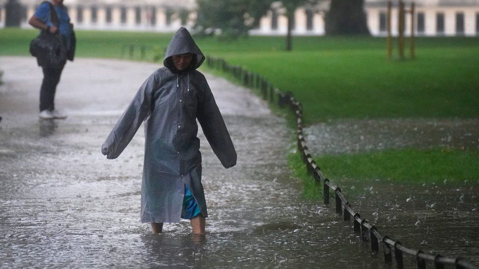A woman wades through a flooded path in St James's Park in central London