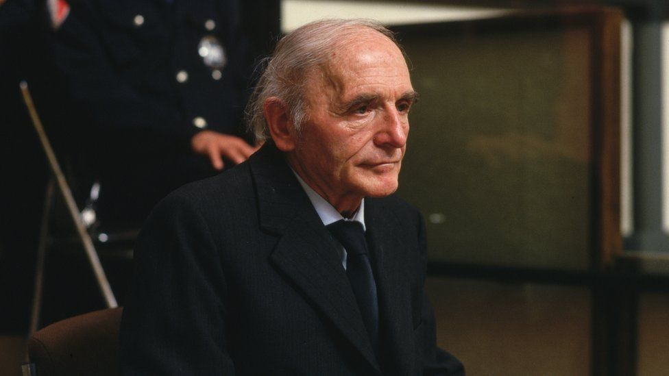 Klaus Barbie sitting behind a glass in court