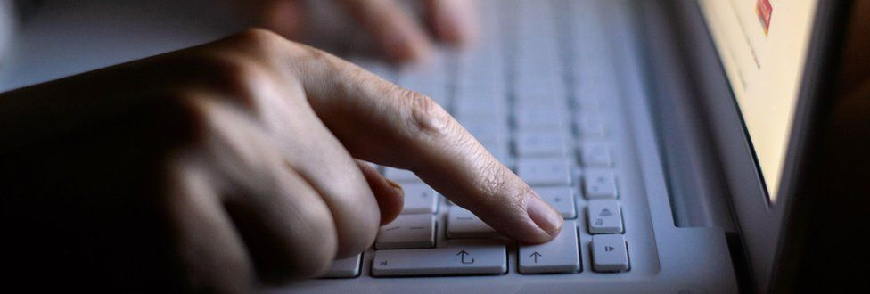 A hand pressing a key on a laptop keyboard