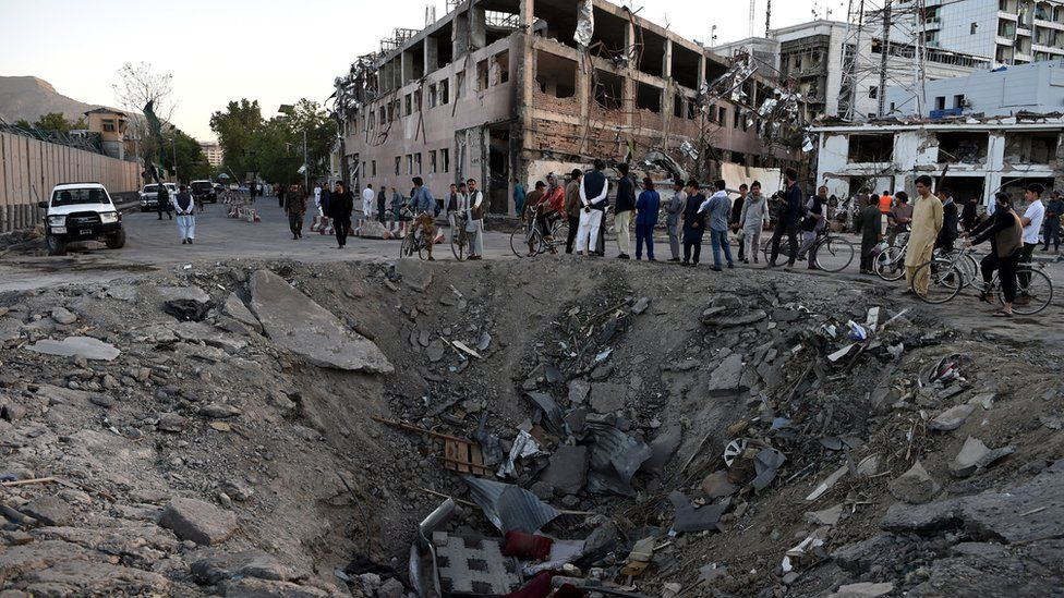 Afghan security forces and residents stand near the crater left by a truck bomb attack in Kabul, 31 May 31 2017