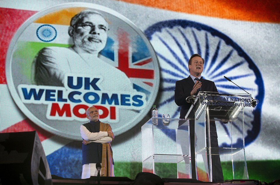 David Cameron, right, addresses the crowd at the rally for Narendra Modi, left