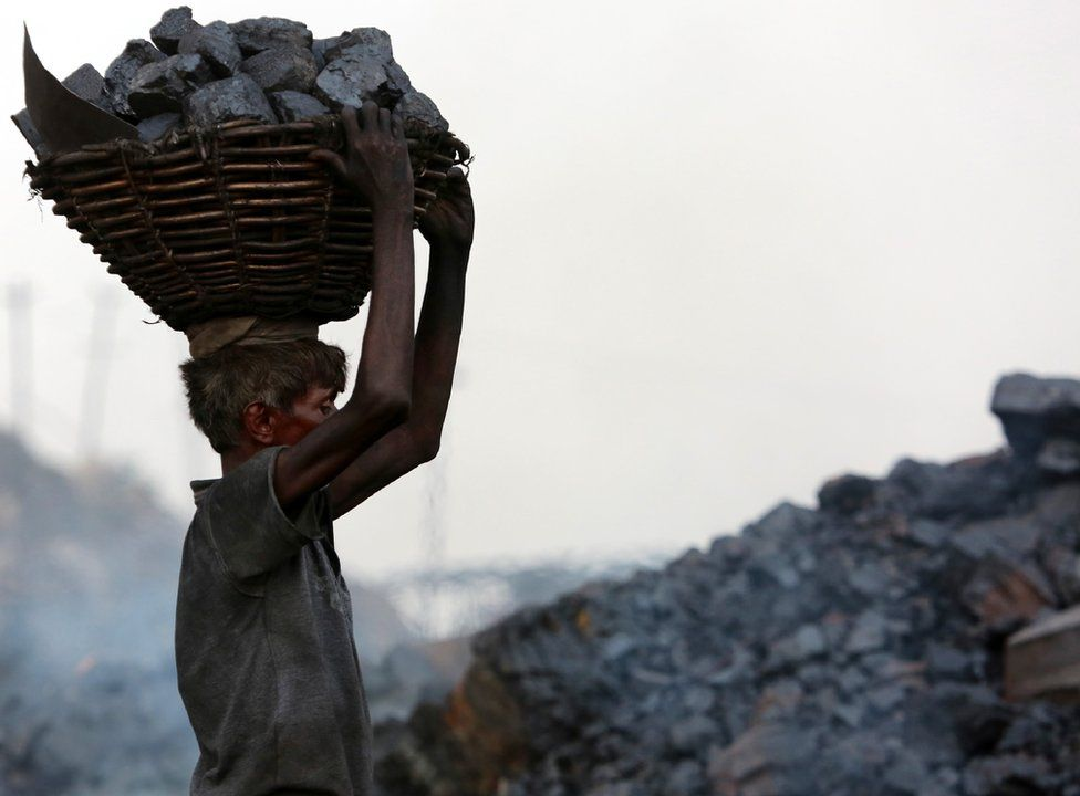 An Indian worker carries a basket of coal collected at a mine in the state of Jharkhand.