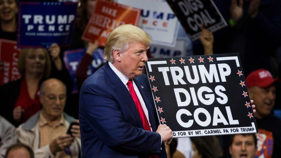 """Donald Trump holds a sign reading """"Trump digs coal"""" at an election campaign rally in 2016"""