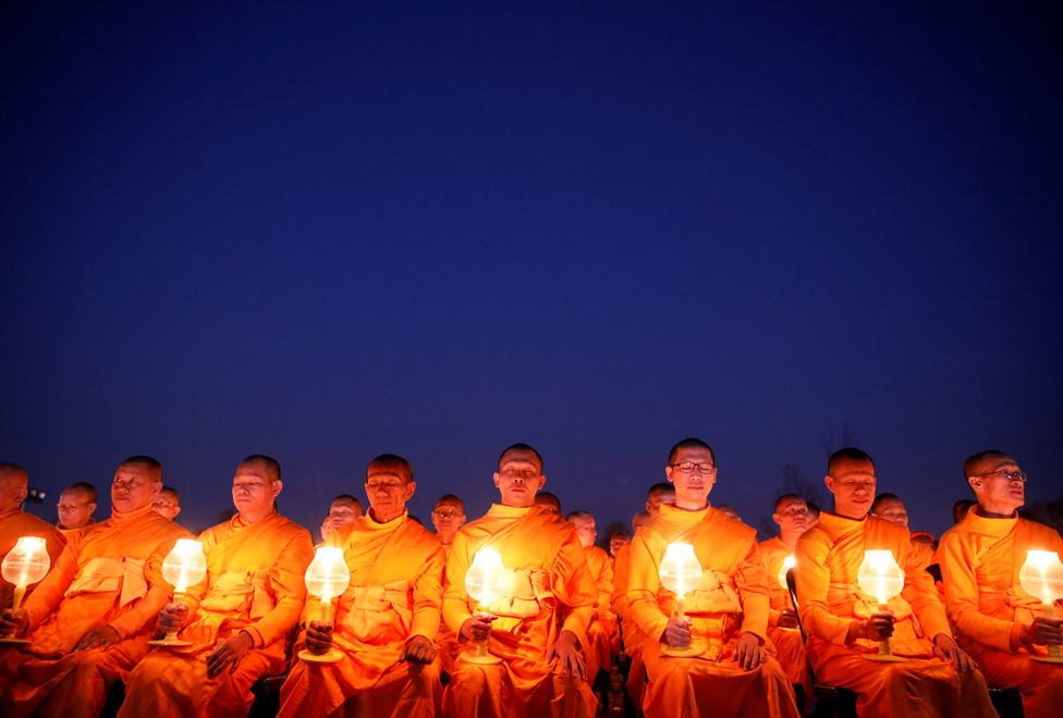 """Monks with lit candles attend an event to spread the message of """"world peace through inner peace"""" in Kathmandu, Nepal, 16 March 2019."""