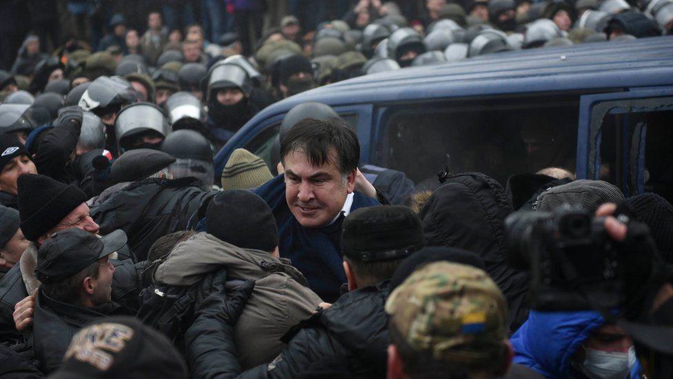 Georgian former President Mikheil Saakashvili struggles out of a police car in Kiev