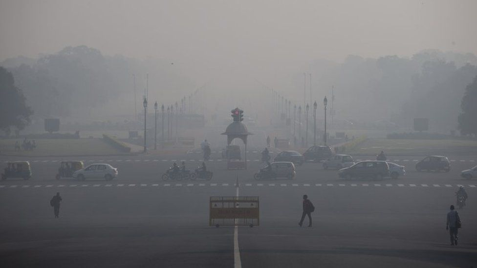 In this Nov. 24, 2015 photo, commuters walk as vehicles move at a traffic signal in New Delhi, India
