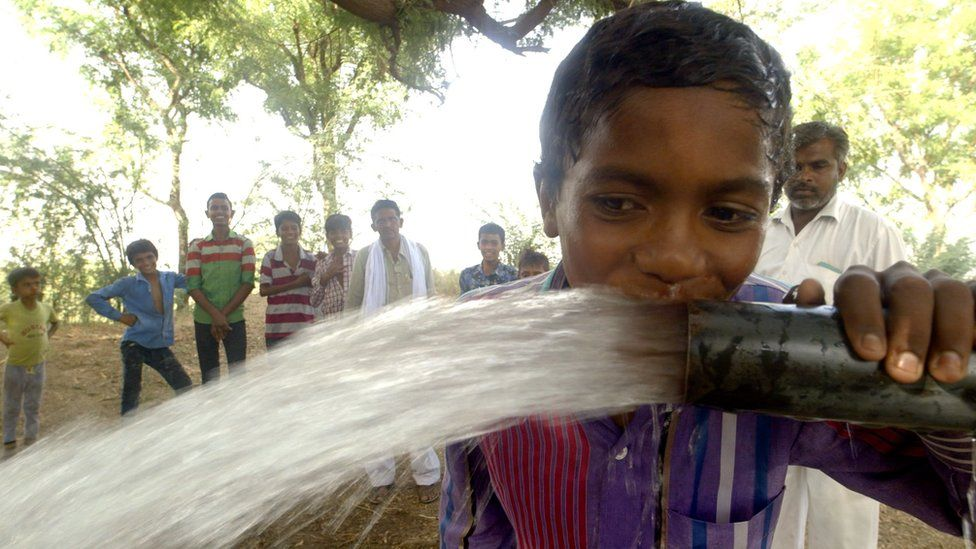A child drinking from a pipe