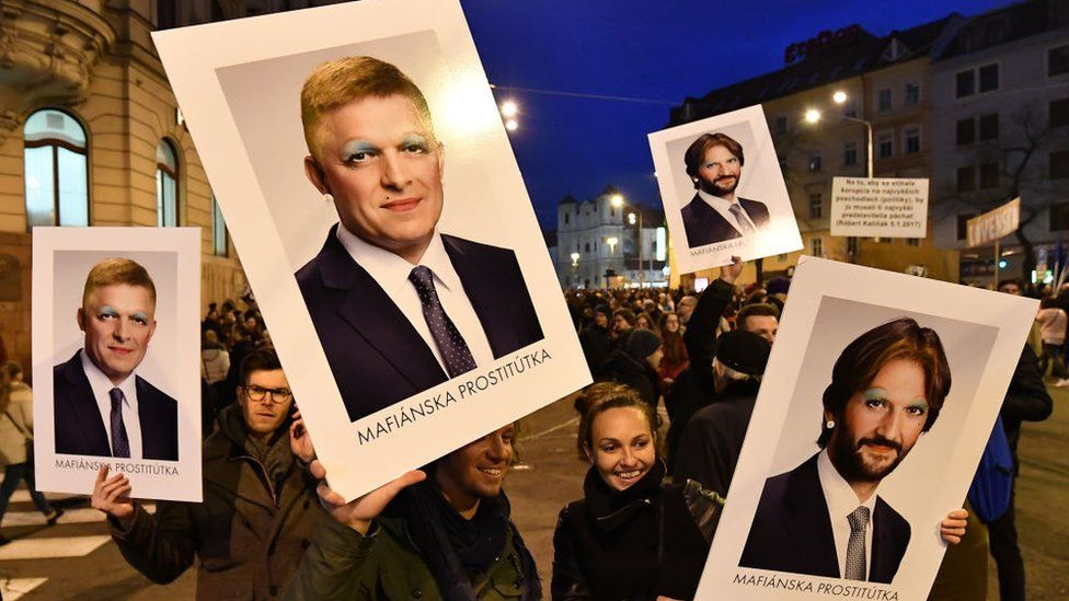 Protesters carry signs depicting Prime Minister Robert Fico, left, and interior minister Robert Kalinak