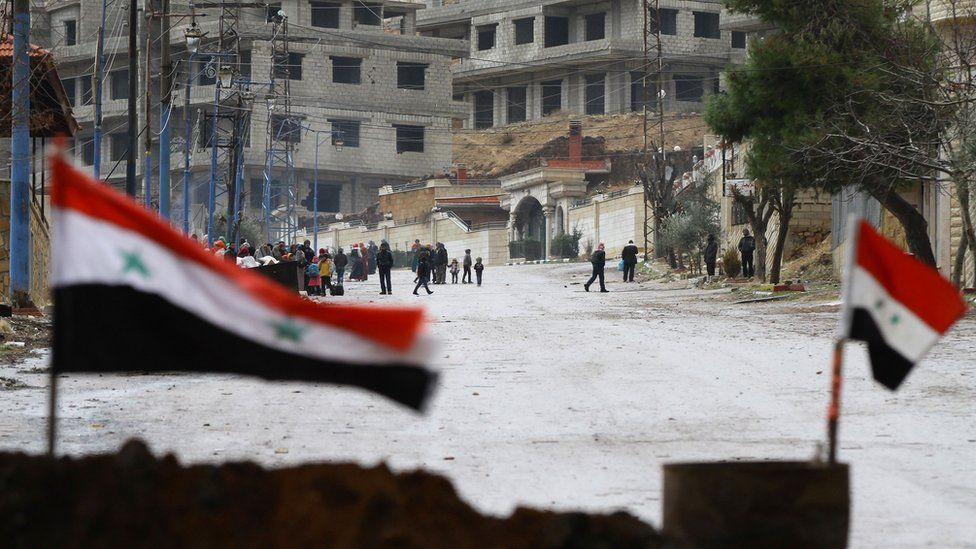 Syrian national flags flutter on a barricade erected at the entrance of the besieged rebel-held Syrian town of Madaya as residents wait for a convoy of aid from the Syrian Arab Red Crescent on 14 January