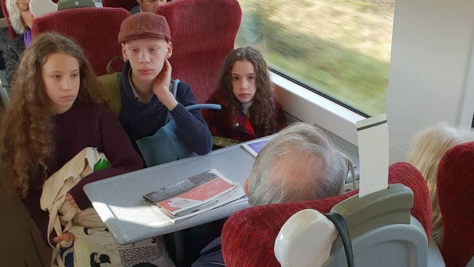 amanda mancino-william's children stare at a couple who refused to leave their reserved seats
