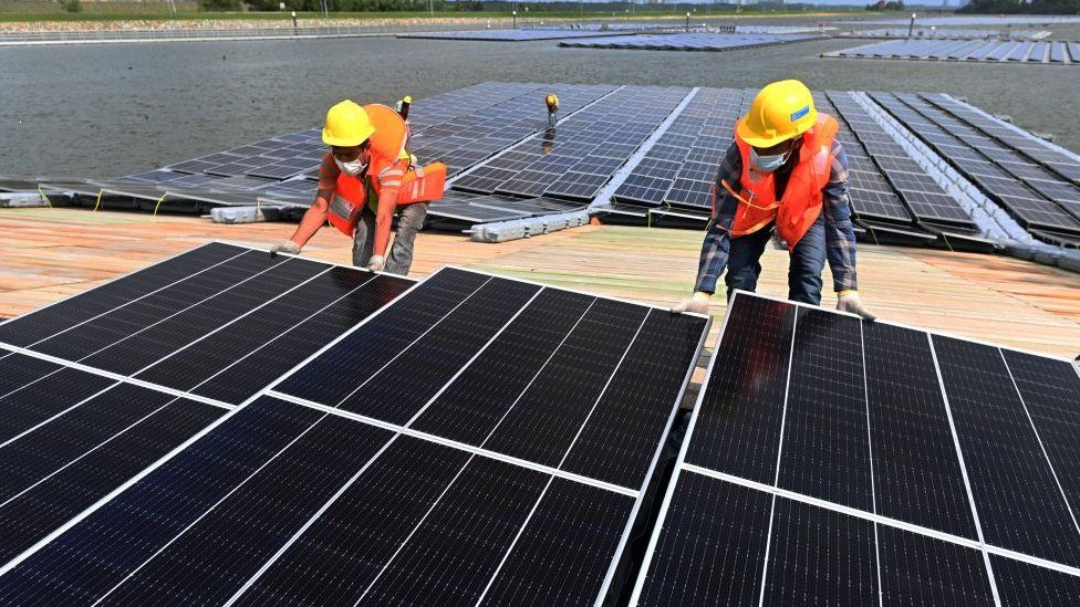 workers assemble solar panels in Singapore