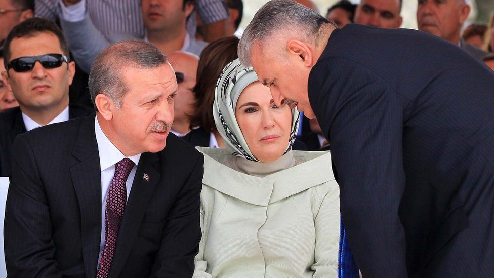 Turkish Prime Minister Recep Tayyip Erdogan (L), flanked by his wife Emine, talks with Turkish Transport Minister Binali Yildirim at event in 2013