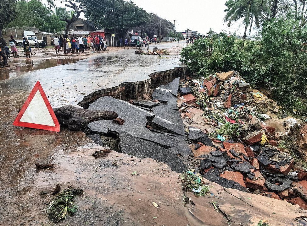 Residents stand next to a road partially destroyed by floods after heavy downpours in Pemba